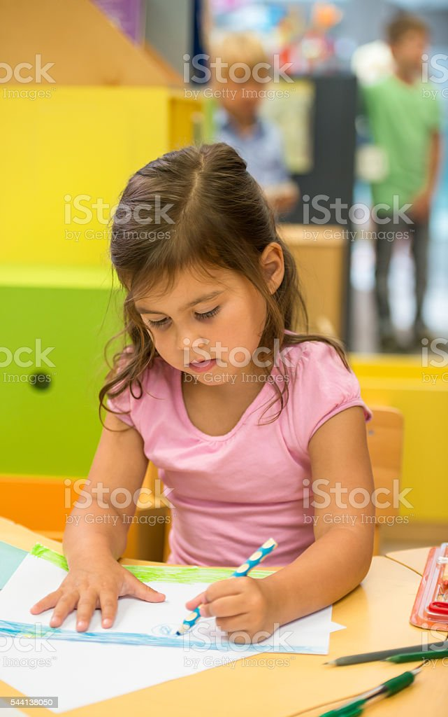 Little Girl Drawing In Library stock photo