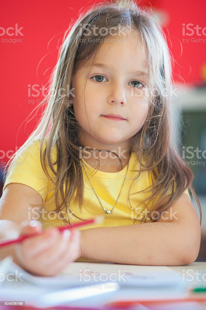 Little girl drawing in the classroom stock photo