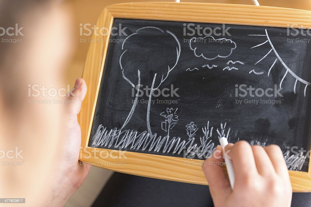 Little girl drawing on chalkboard royalty-free stock photo