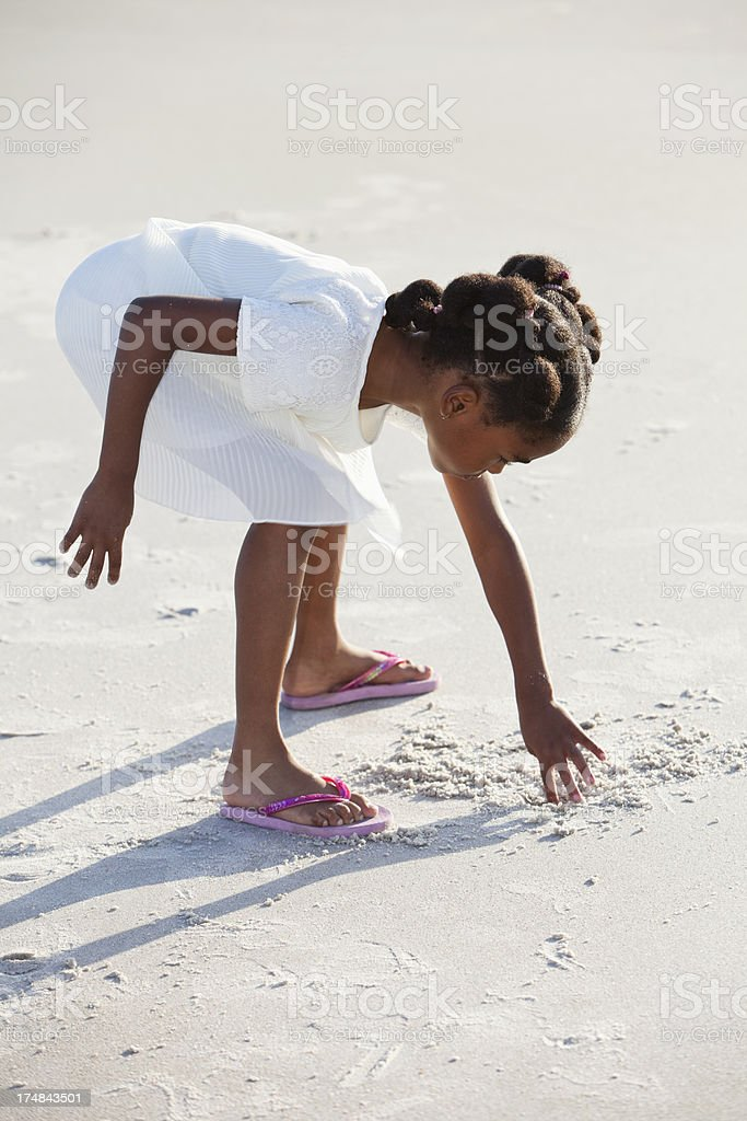 Little girl drawing pictures in sand stock photo