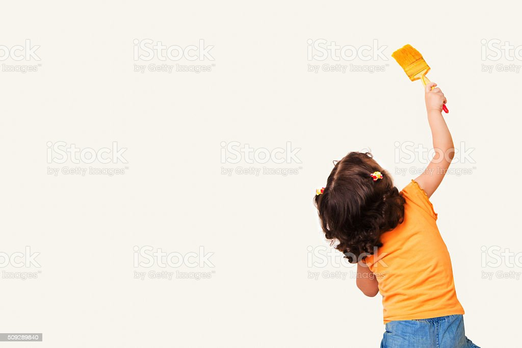 Little girl drawing something on wall background stock photo