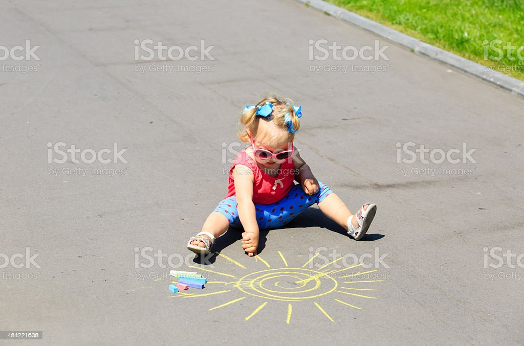 little girl drawing sun with chalks on a street stock photo