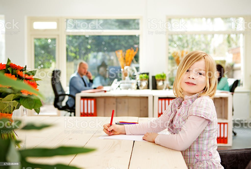 little girl drawing while her parents working stock photo