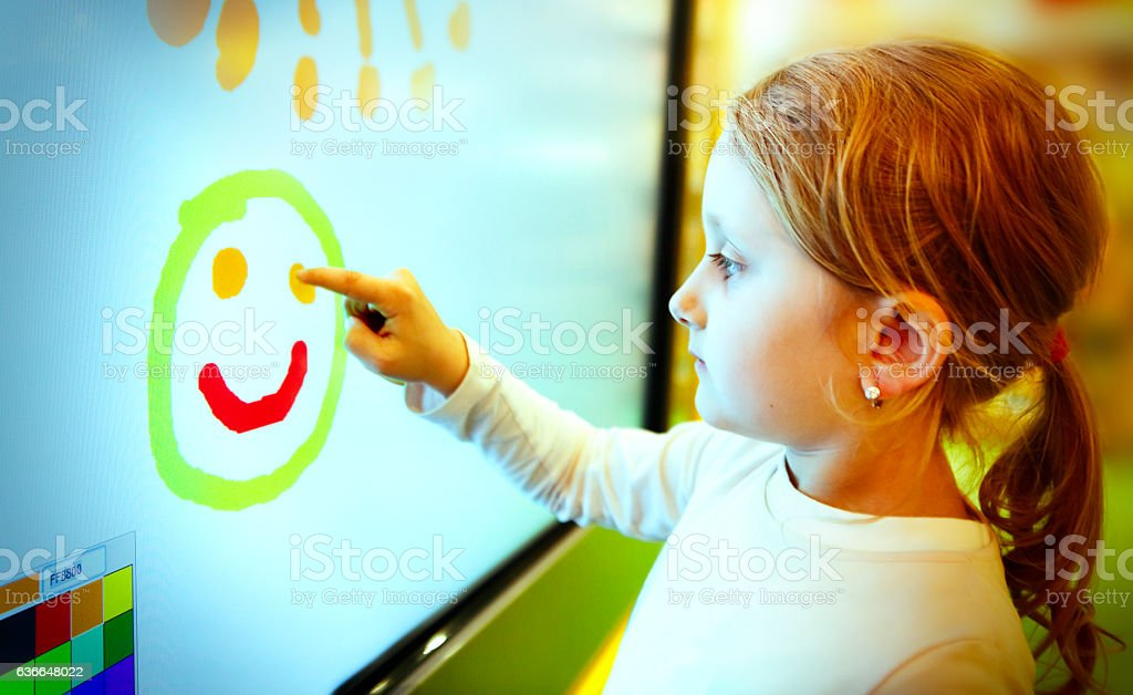 Little girl drawing with finger on the touch screen stock photo