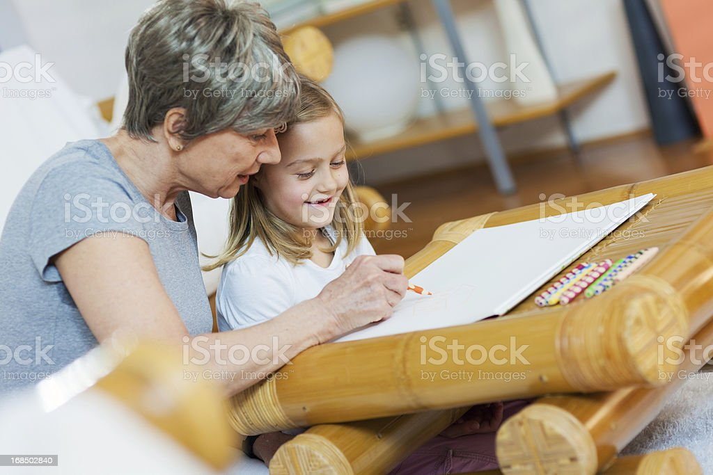 Little Girl Drawing With Her Grandmother royalty-free stock photo
