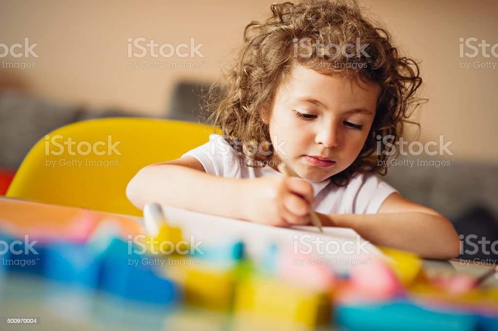 Little girl drawing with pencil stock photo