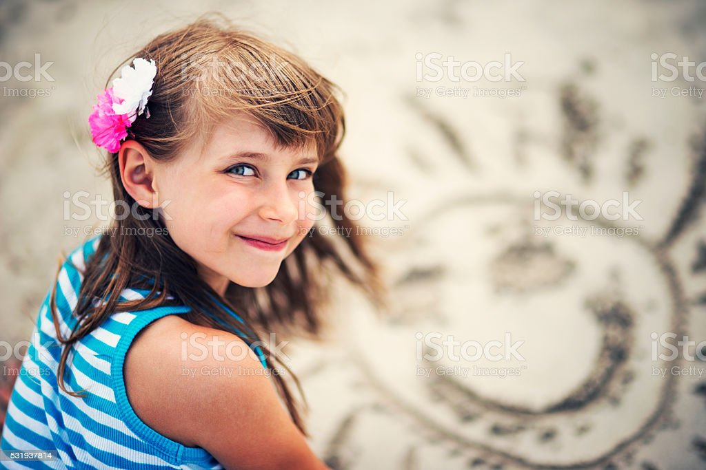 Little girl drawingh sun in the sand on the beach. stock photo