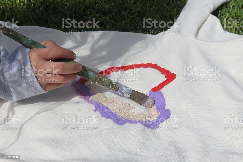 little girl draws on a shirt stock photo