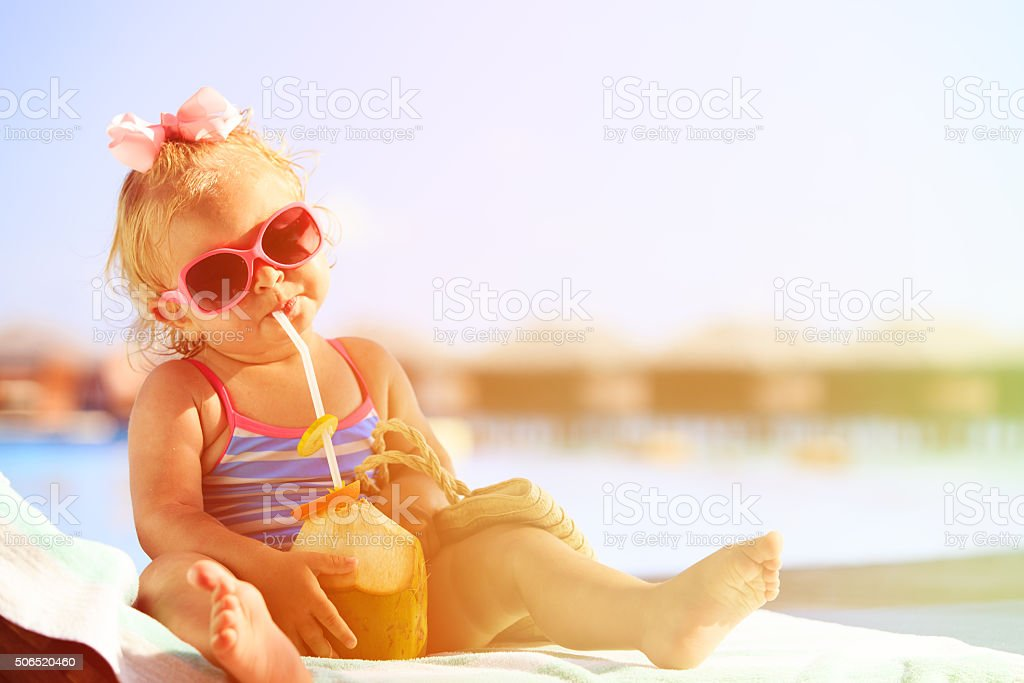 little girl drinking coconut cocktail on beach stock photo