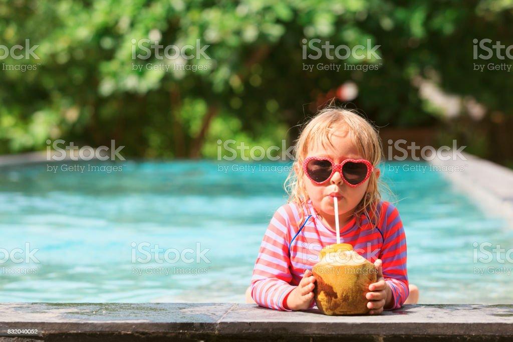 little girl drinking coconut cocktail on beach resort stock photo