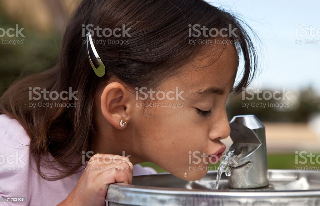 Little girl drinking from a water fountain stock photo
