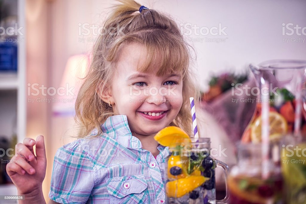 Little Girl Drinking Infused Water with Fresh Blueberries and Oranges stock photo