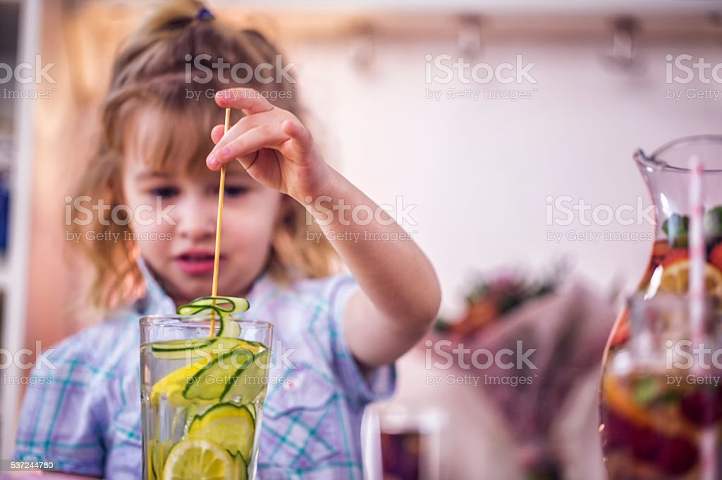 Little Girl Drinking Infused Water with Fresh Cucumber and Lemon stock photo