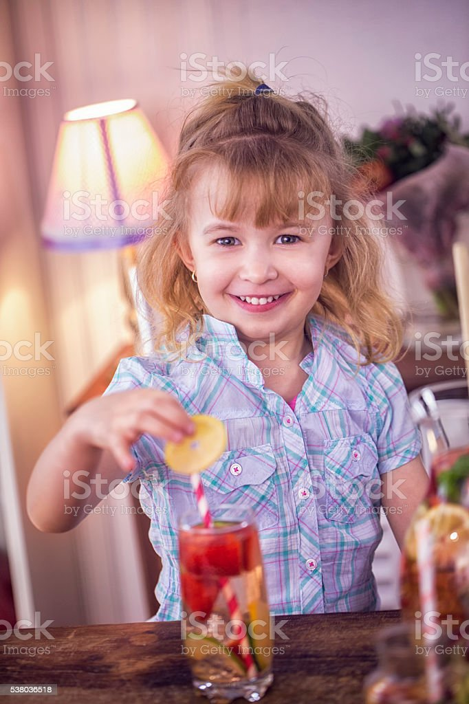 Little Girl Drinking Infused Water with Fresh Strawberries and Lemon stock photo