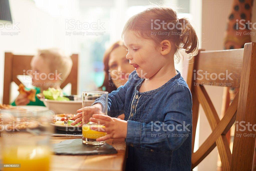 little girl drinking juice at dinner stock photo