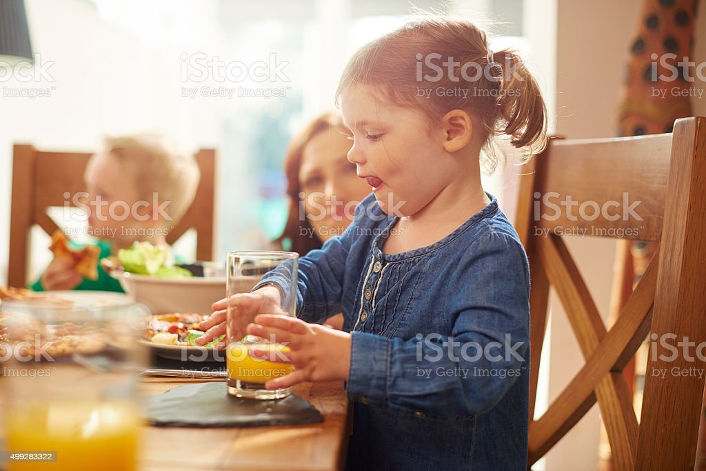 little girl drinking juice at dinner stock photo