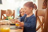 little girl drinking juice at dinner