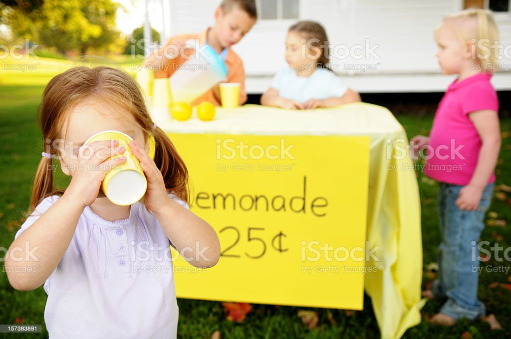Little Girl Drinking Lemonade in Front of a Stand stock photo