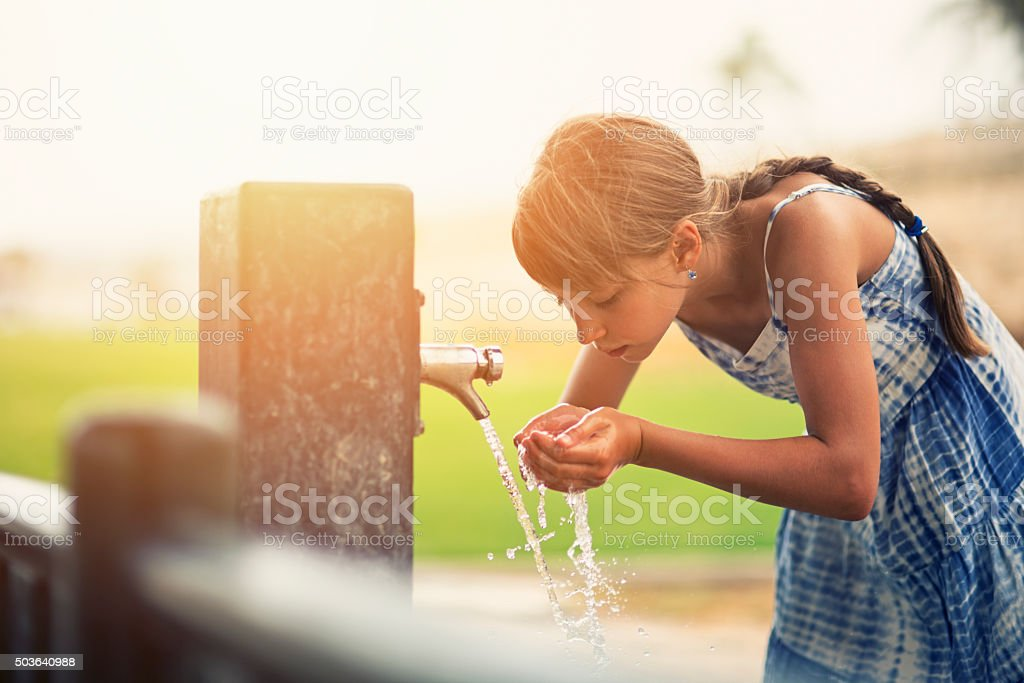 Little girl drinking water stock photo