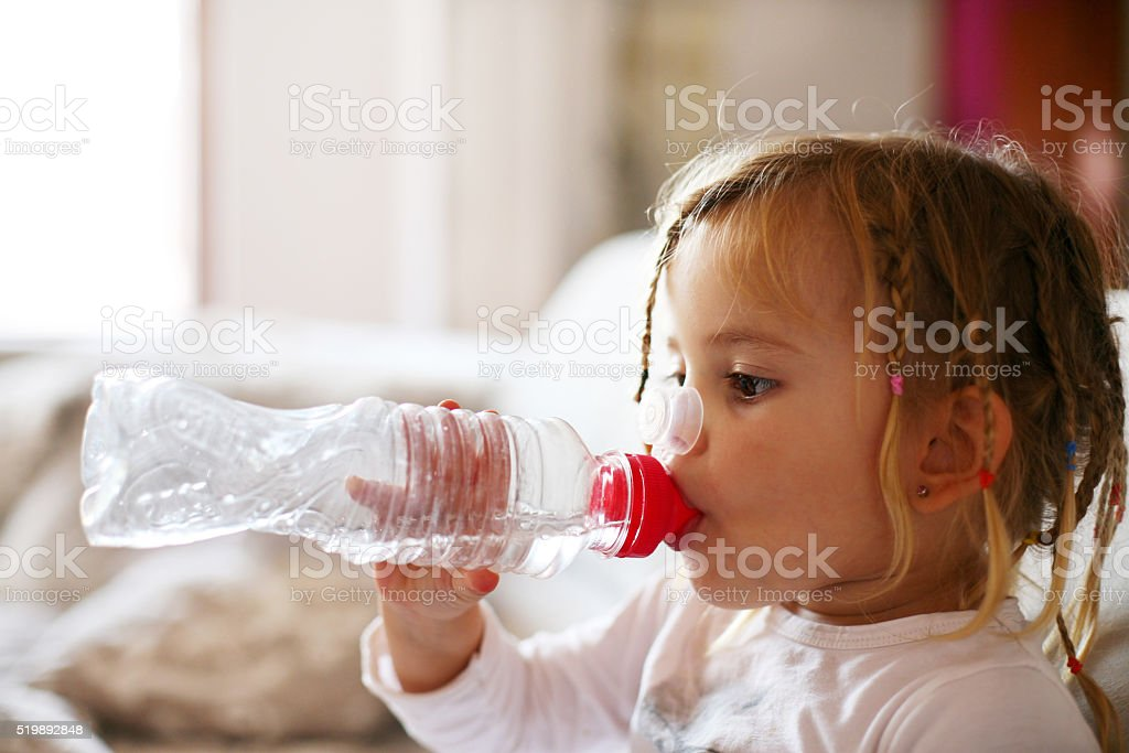 Little girl drinking water. stock photo
