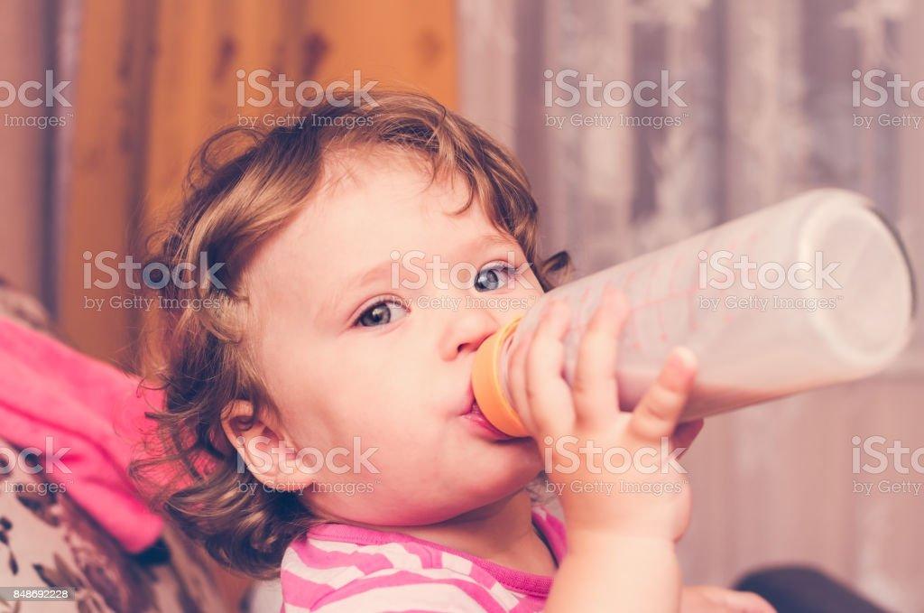 Little girl drinks milk from a bottle stock photo