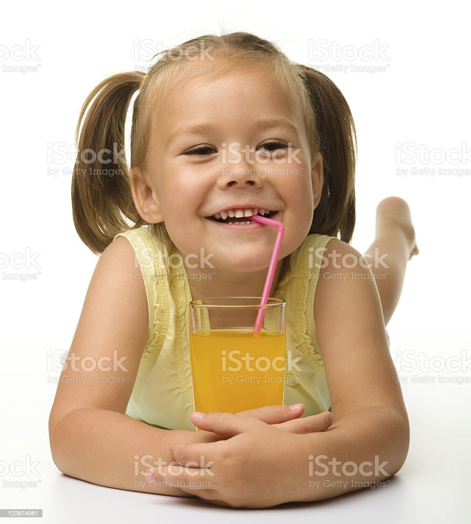 Little girl drinks orange juice royalty-free stock photo