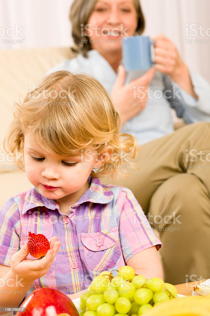 Little girl eat strawberry fruit with grandmother royalty-free stock photo