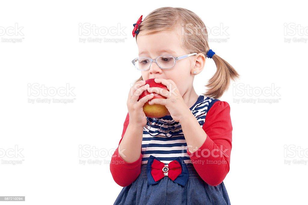 Little girl eating a red apple photo libre de droits