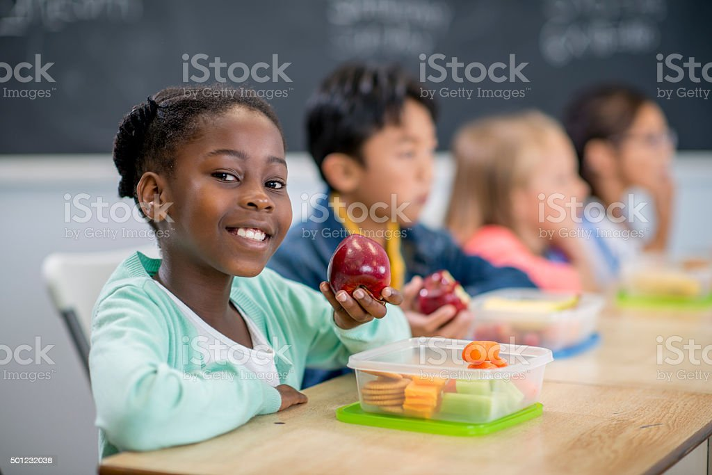 Little Girl Eating an Apple in Class stock photo