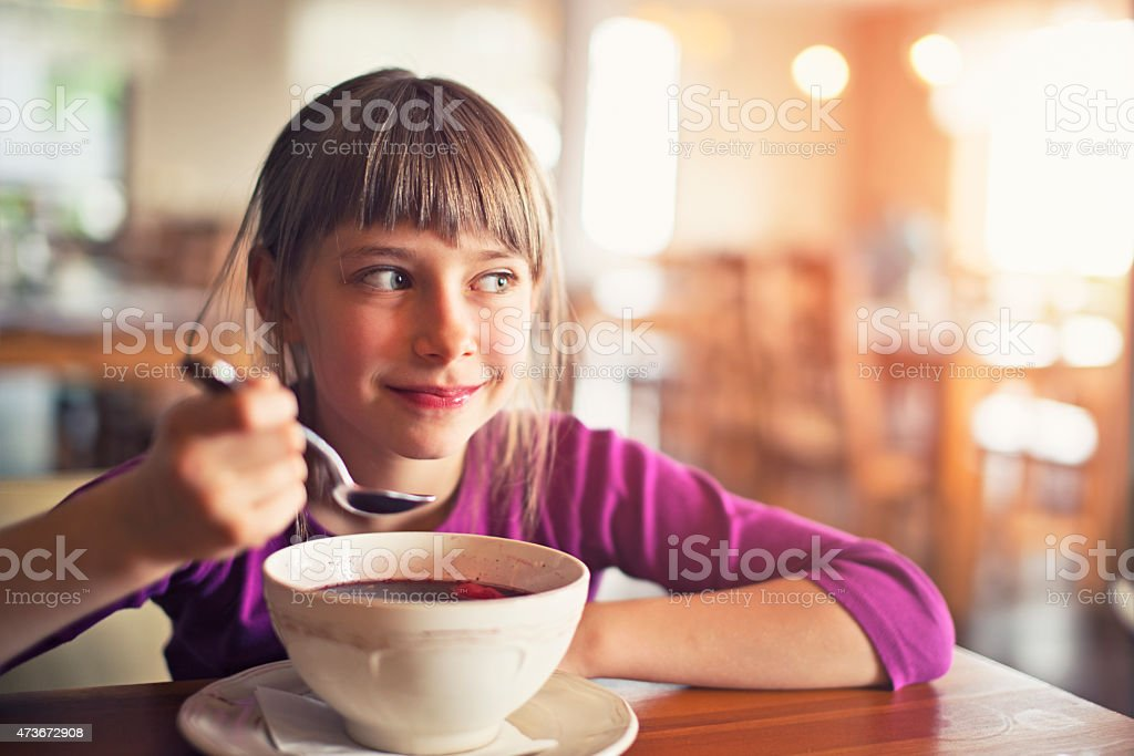 Little girl eating beetroot soup stock photo