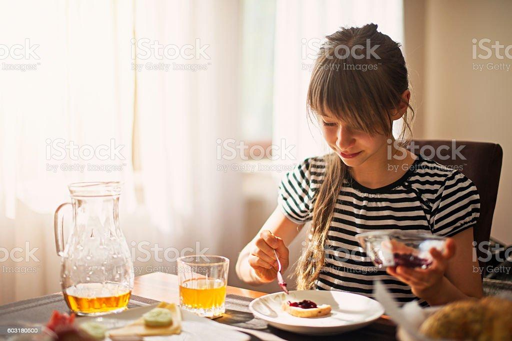 Little girl eating breakfast on sunny morning stock photo