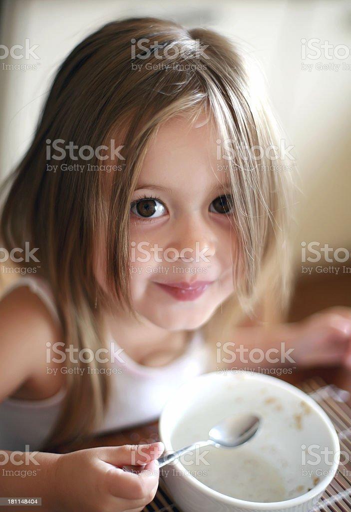 Little girl eating breakfast stock photo