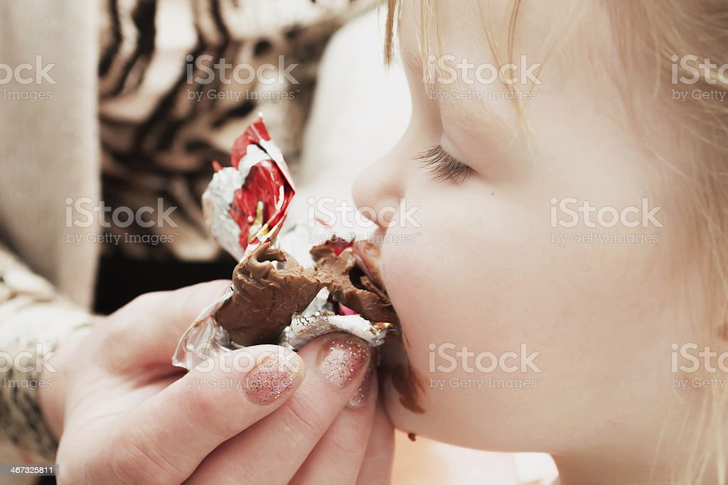 little girl eating chocolate candy. Pleasure. stock photo