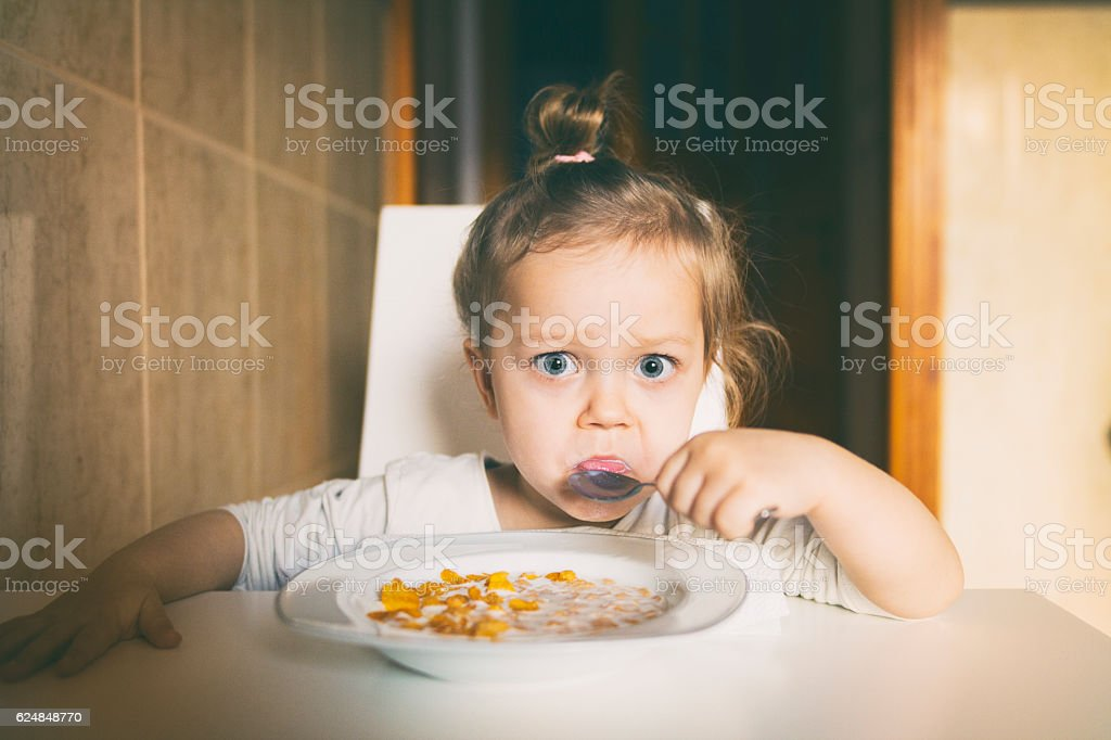 Little girl eating corn flakes stock photo