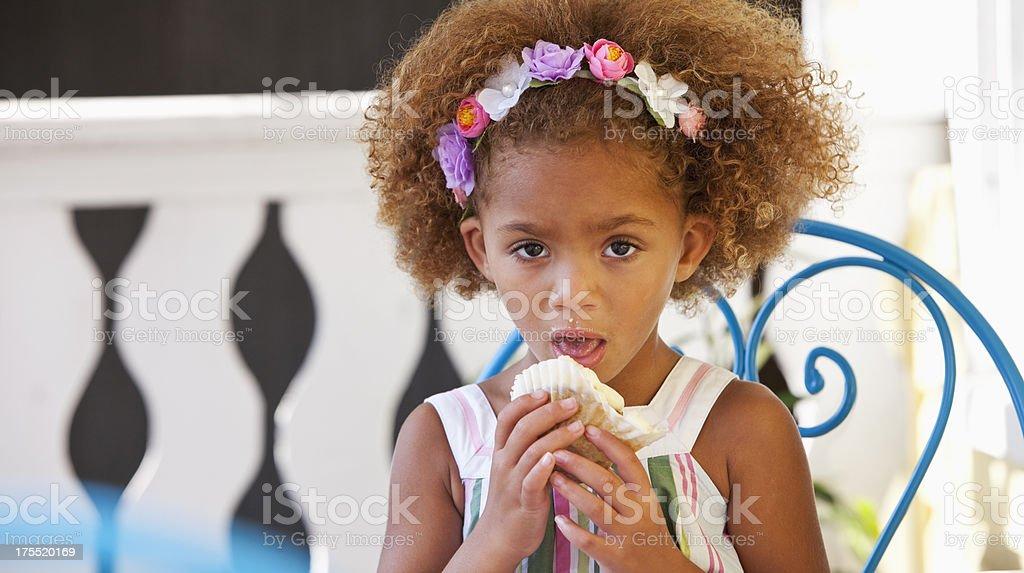 Little girl eating cupcake stock photo
