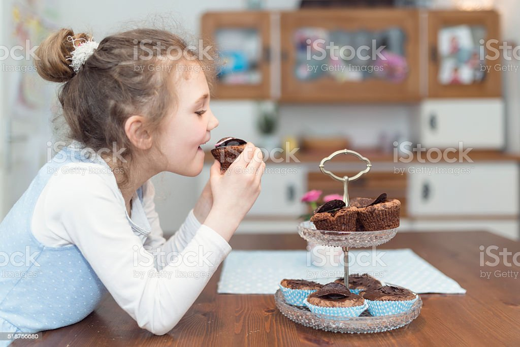little girl eating cupcakes stock photo