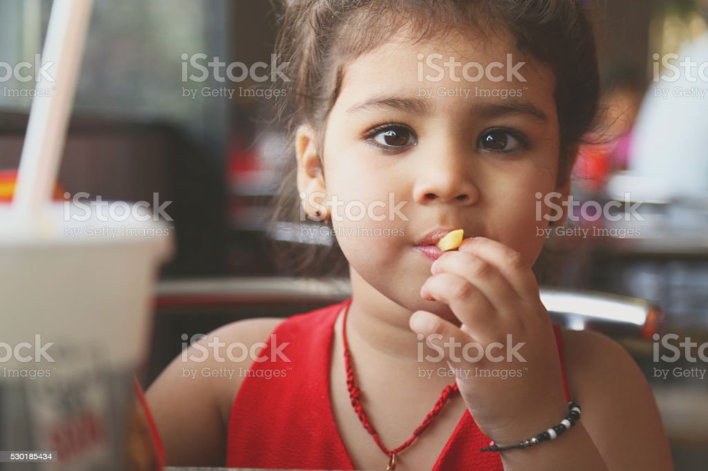 Little girl eating French fries stock photo