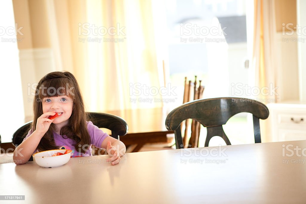 Little Girl Eating Fruit at Counter in Her Kitchen royalty-free stock photo