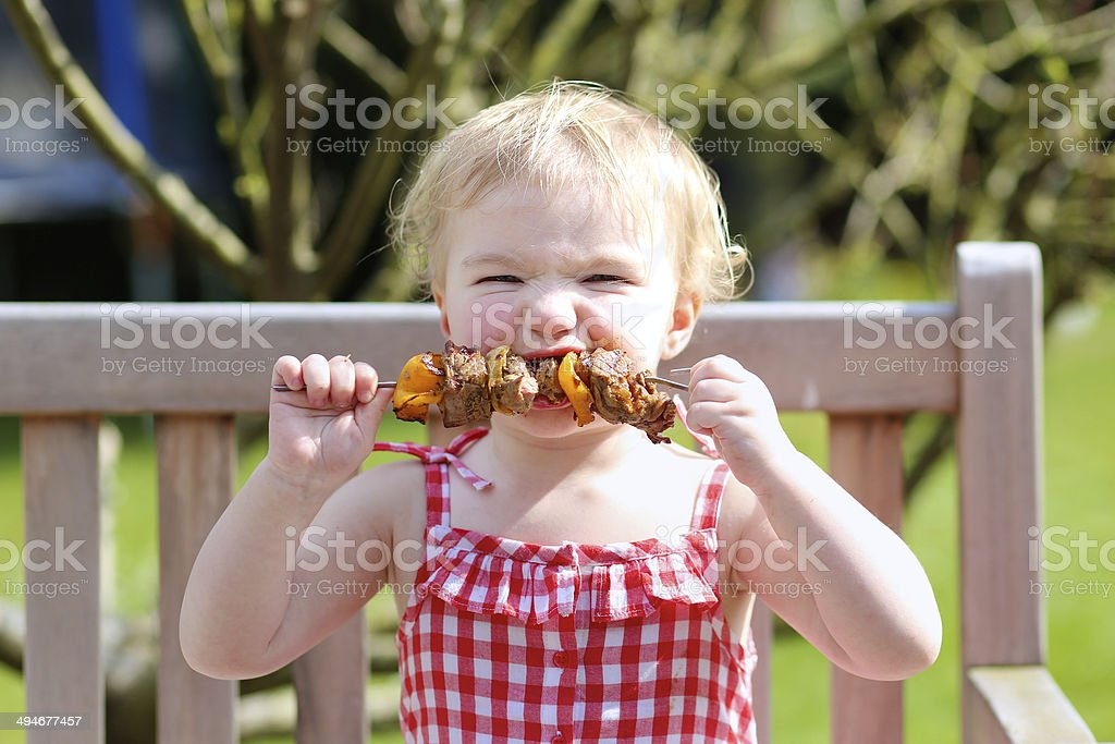 Little girl eating grilled meat outdoors stock photo