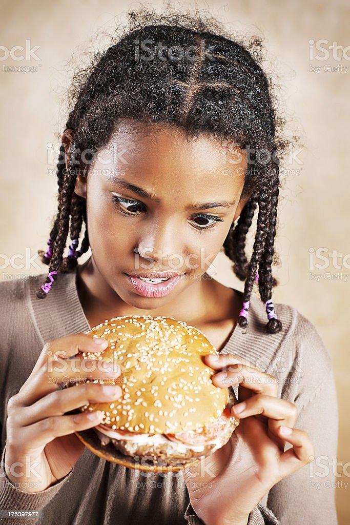 Little girl eating hungrily looking at hamburger. royalty-free stock photo