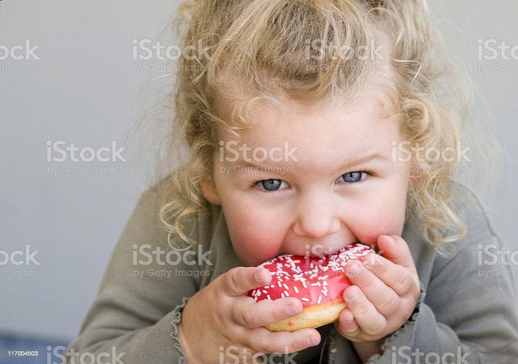 Little girl eating jelly-glazed donut with sprinkles stock photo