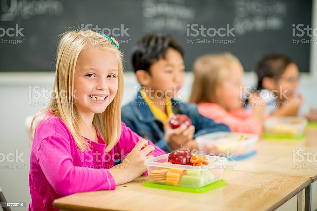 Little Girl Eating Lunch at School stock photo