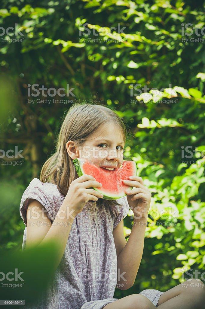 little girl eating melon stock photo
