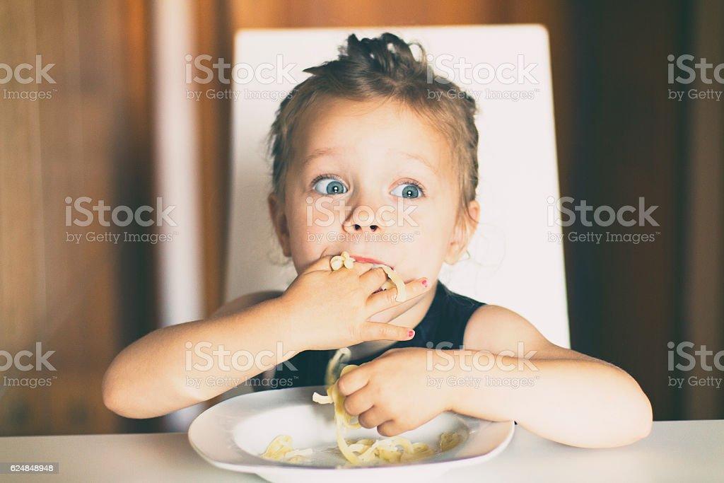 Little girl eating pasta stock photo
