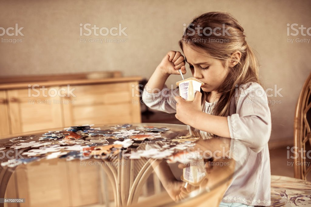 Little girl eating pudding after playing with jigsaw puzzles. stock photo