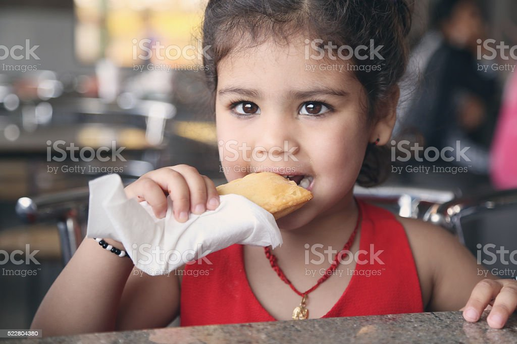 Little girl eating puff food stock photo