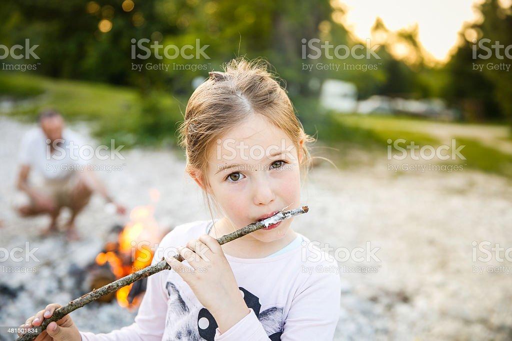Little girl eating roasted marshmallow stock photo
