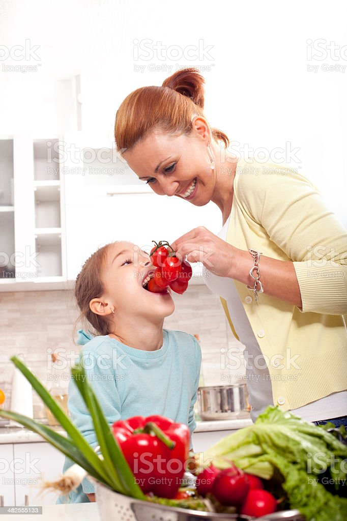 little girl eating tomato  in the kitchen royalty-free stock photo