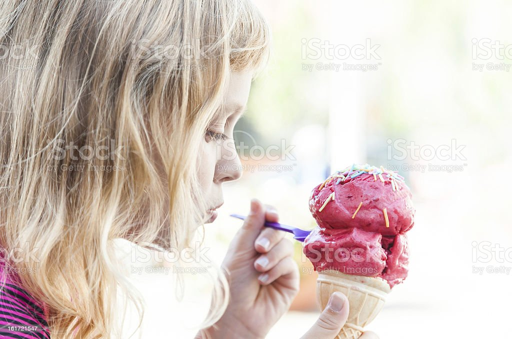 Little girl eats big ice-cream in the park royalty-free stock photo