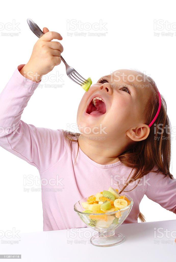 Little girl eats fruit salad stock photo